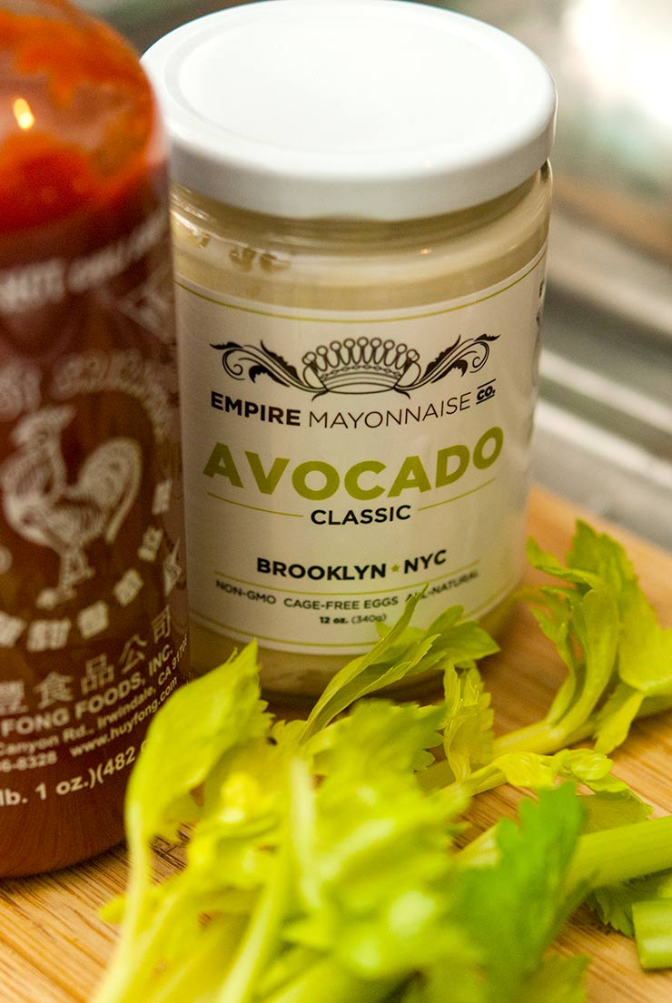 Avocado mayonnaise next to a bottle of Sriracha behind celery leaves on a cutting board.