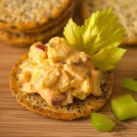 A cracker with sriracha egg salad and a celery leaf in front of small stacks of crackers on a wooden plate.