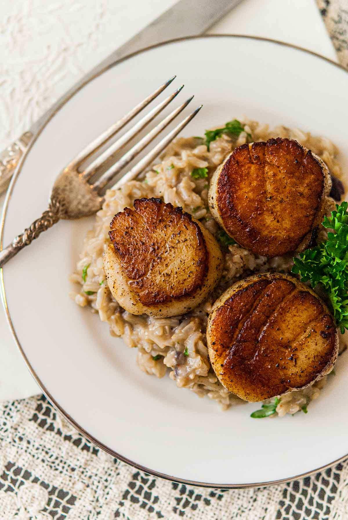 3 seared scallops on top of creamy rice, garnished with a sprig of parsley, on a place beside an antique fork.