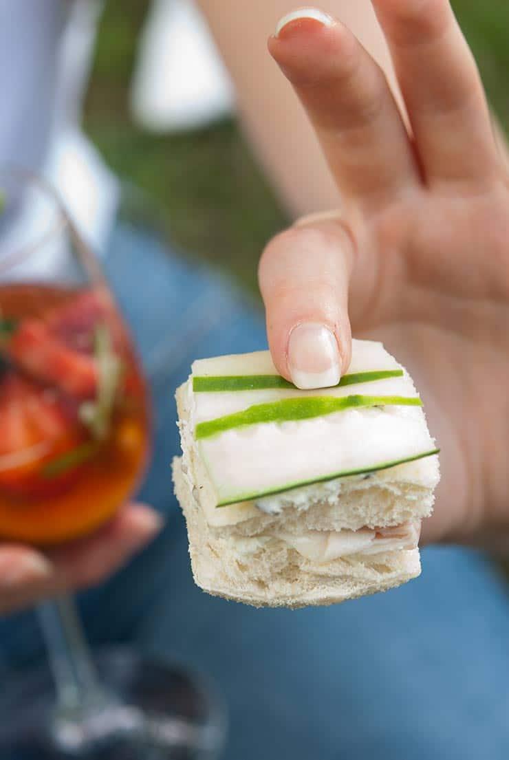 A woman's hand holding a cucumber sandwich.