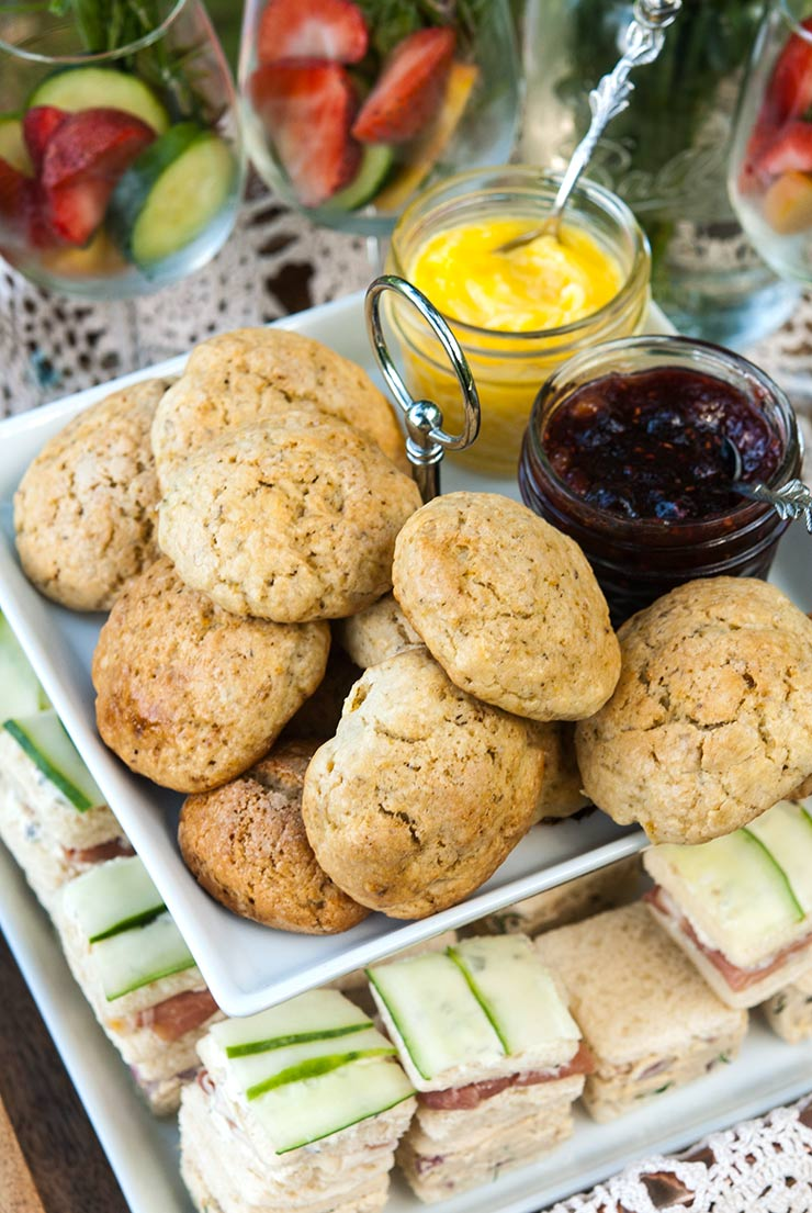 A appetizer tier with scones on top and cucumber sandwiches on the bottom, with cocktail glasses beside it.