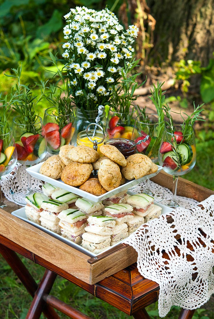An appetizer tier on a tray with lace, holding scones and cucumber sandwiches, surrounded by garnished cocktail glasses and a vase holding daisies in a wooded setting.