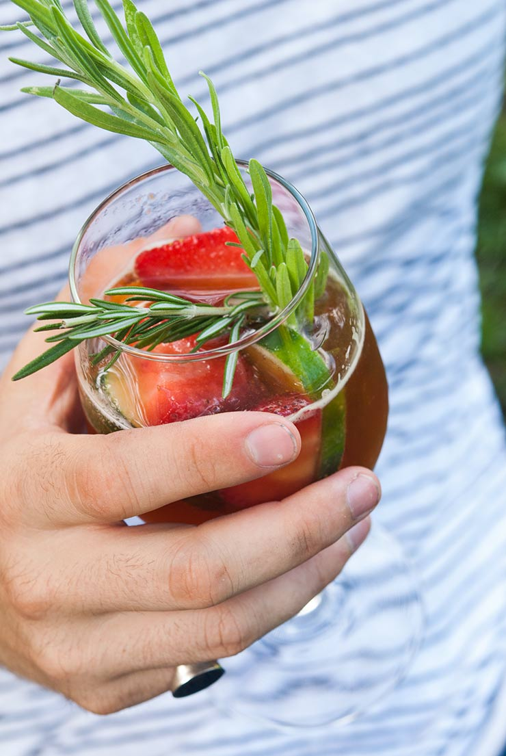 A hand holding a strawberry Pimms Cup cocktail with fruit and herb garnishes in front of a striped shirt.