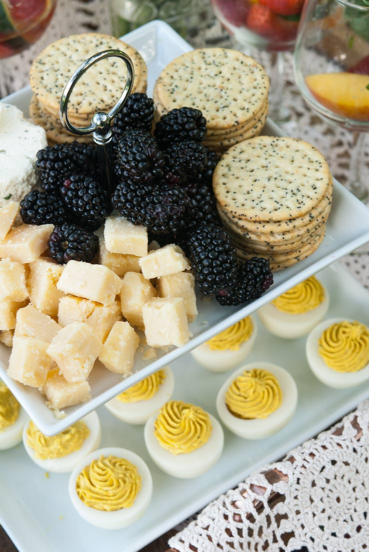 2 appetizer tiers. One with cheese, blackberries and crackers, and the one below, with deviled eggs.