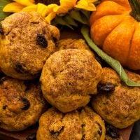 Pumpkin scones beside a small pumpkin and sunflower on a wooden board.