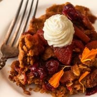 Cranberry apple crisp on a plate, topped with whipped cream and sprinkled with marigold flower petals.