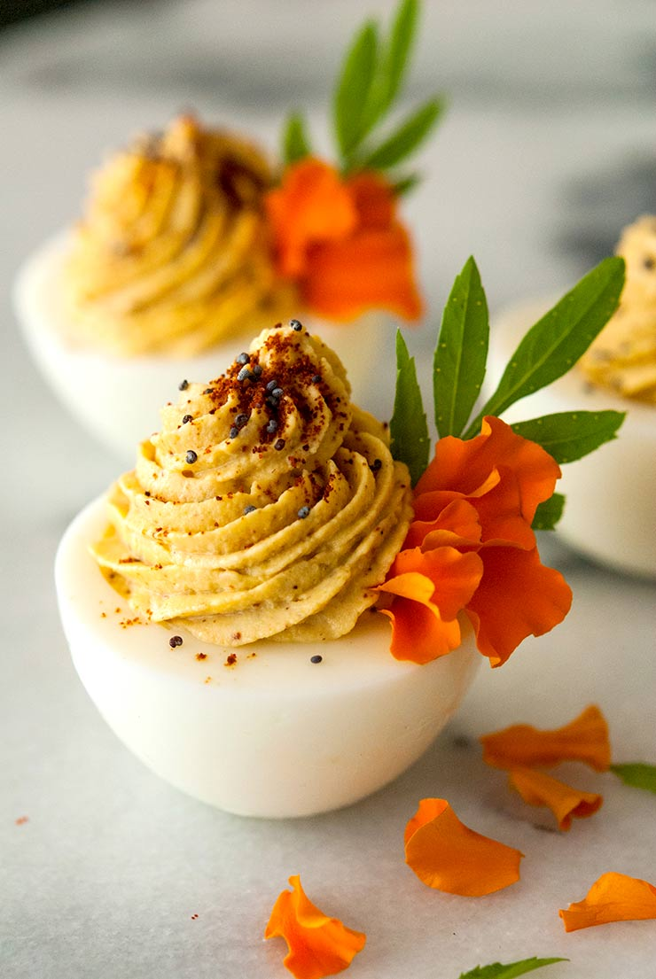 Deviled eggs garnished with marigold petals, spices and leaves on a marble table.