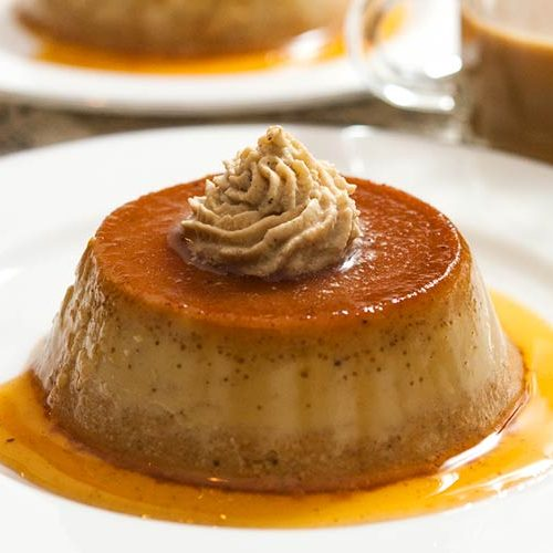 2 pumpkin flans on plates on a table, topped with chai whipped cream, with a small cup of coffee.