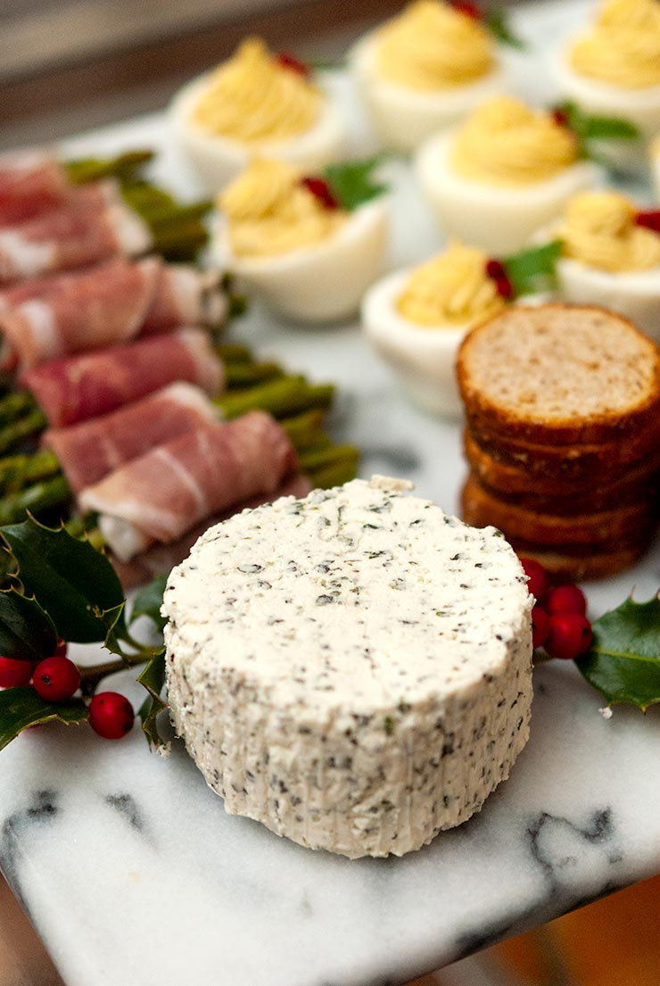 A cheese plate with herbed cheese, prosciutto-wrapped asparagus, crackers and deviled eggs, garnished with holly berries and leaves.