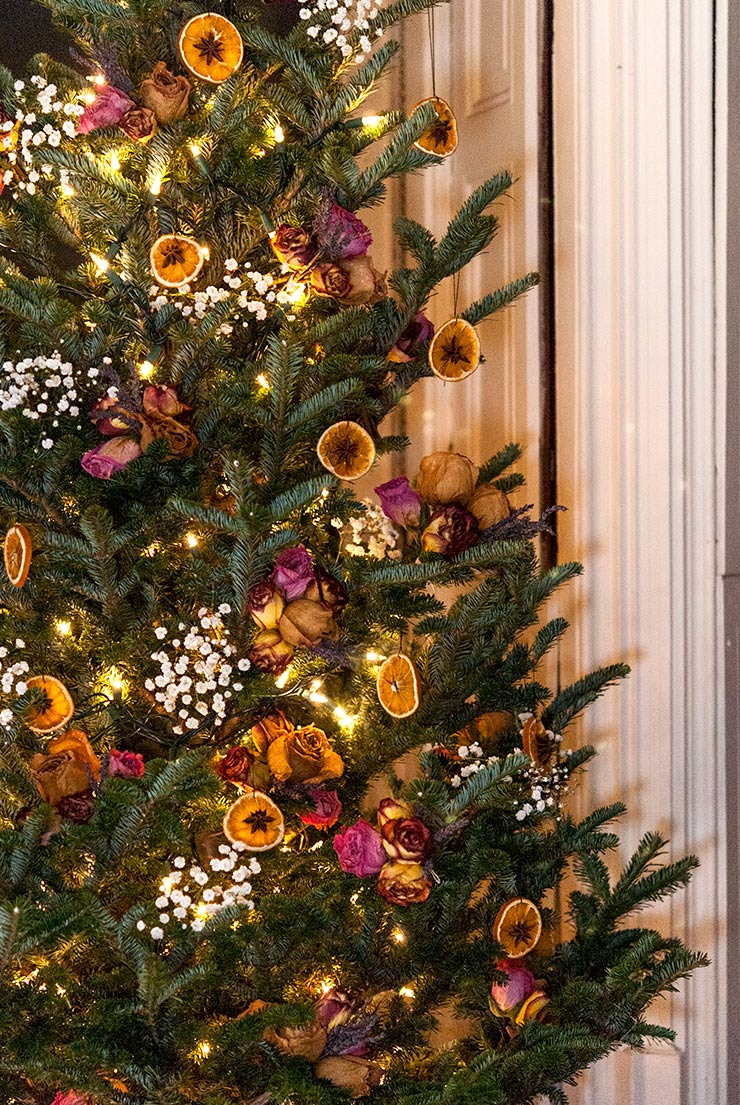 A colorful Christmas tree decorated with flowers and dry orange ornaments.
