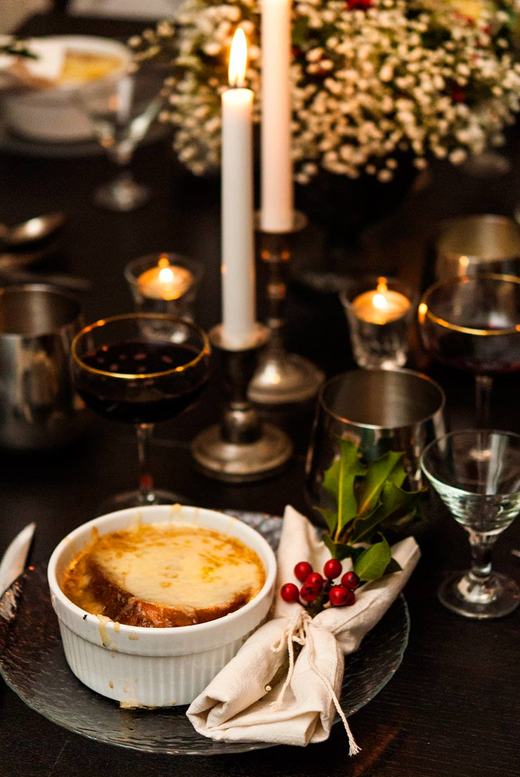 French onion soup on a table lit with candles, surrounded by glassware and Christmas holly decorations.
