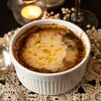 A bowl of French onion soup on a lace table cloth beside candles.