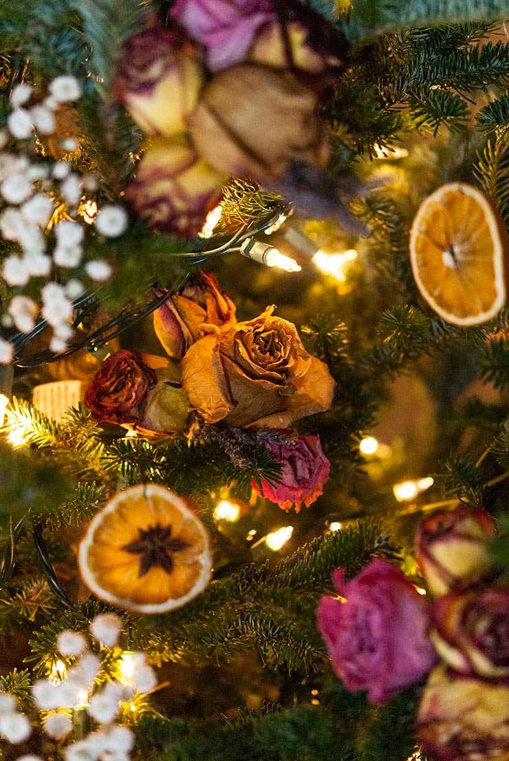 a colorful christmas tree decorated with flowers and dried orange slices.