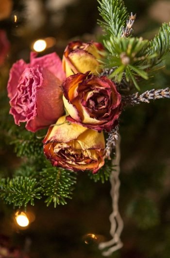 A small bouquet of roses and lavender tied to a Christmas tree bough.