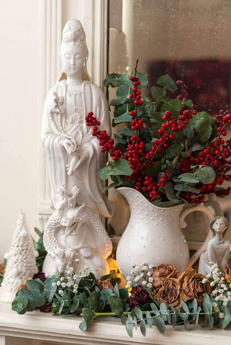 A buddha statue on a mantle surrounded by floral Christmas decorations.