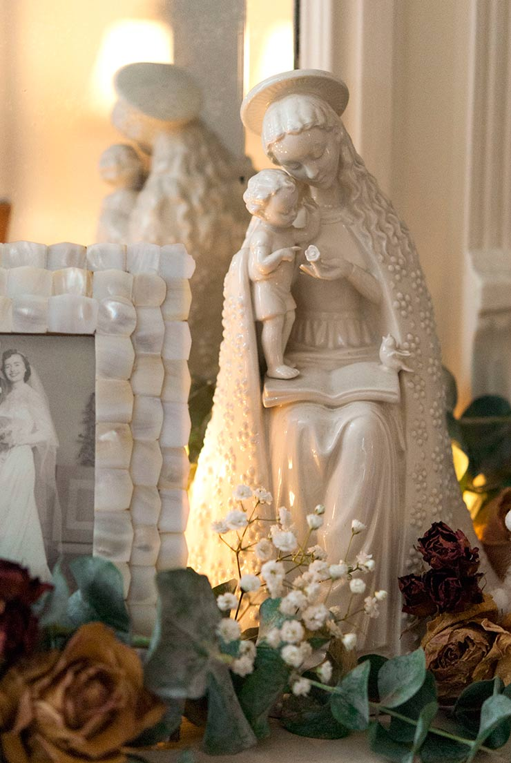 A virgin Mary statue on a mantle beside a vintage wedding photograph, surrounded by flowers.