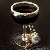 A haunting black cocktail in a coup glass, rimmed with sugar, with dry flowers at its base.