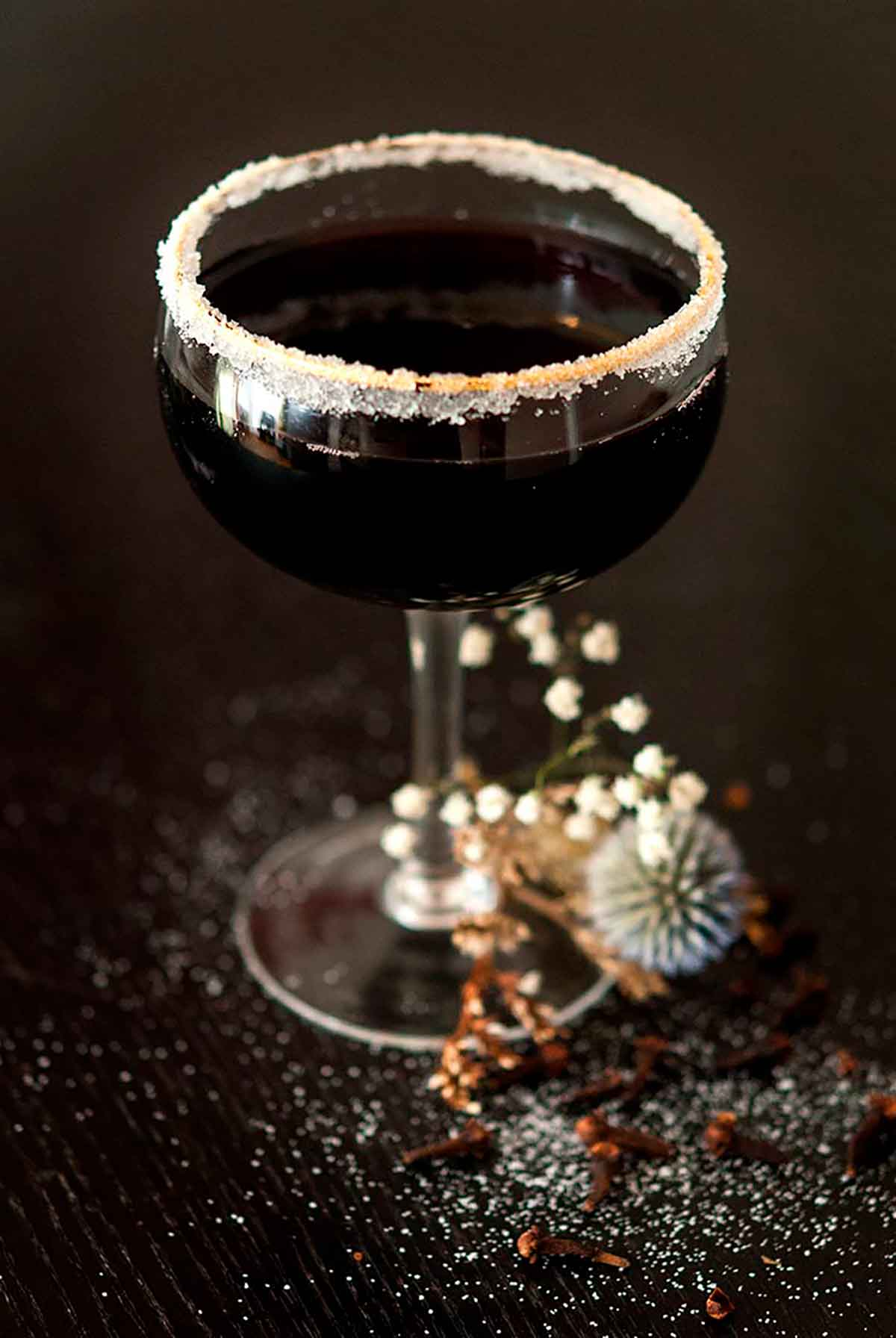 A sugar-rimmed, black cocktail surrounded by dry baby's breath on a sugar-sprinkled table.