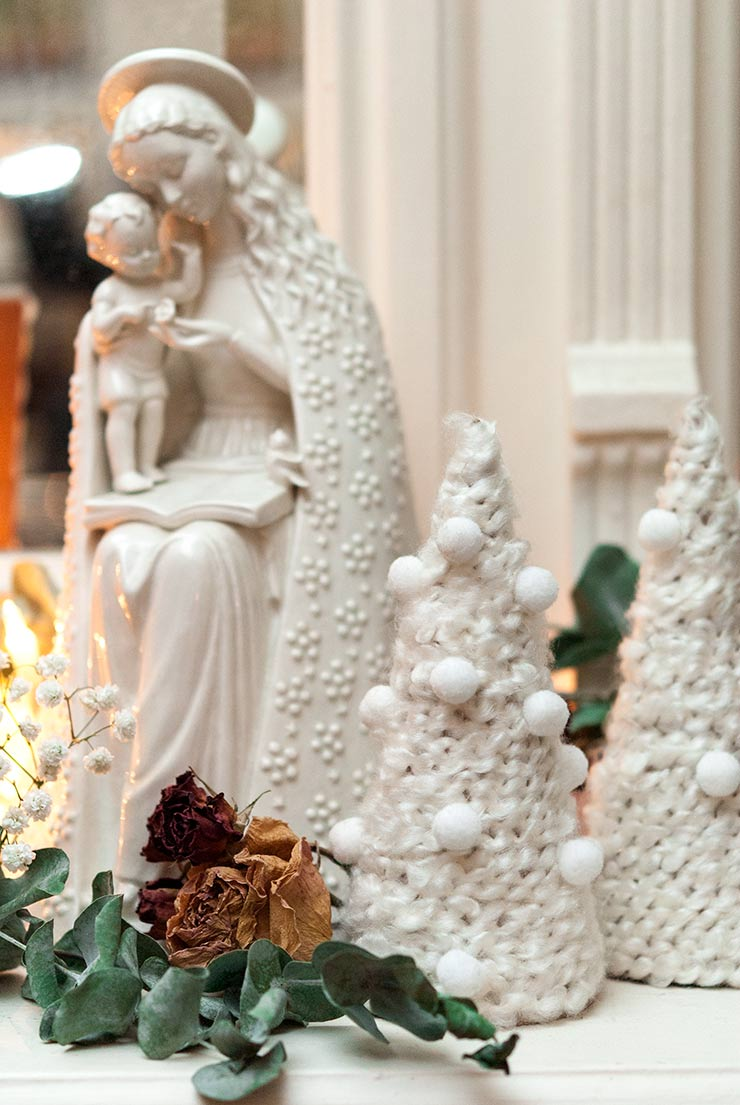 Small christmas trees made of yarn on a mantle decorated with dry roses, eucalyptus and a porcelain Mary statue.