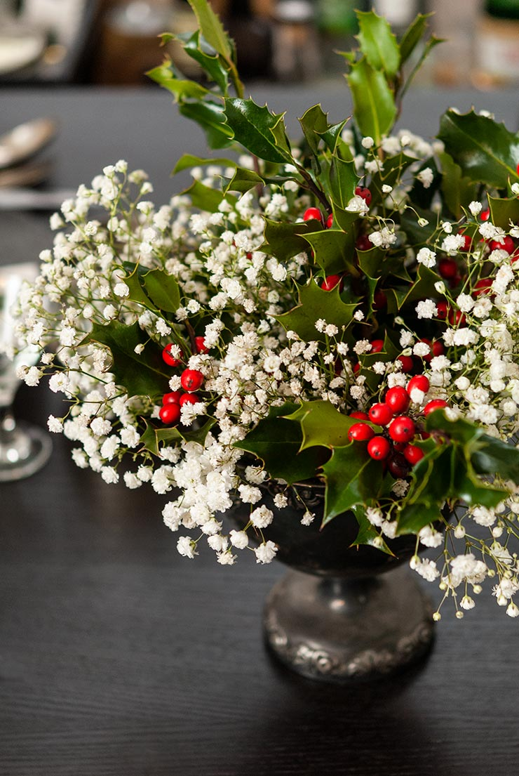 A silver vase with a holly and baby's breath bouquet on a dark wooden table.
