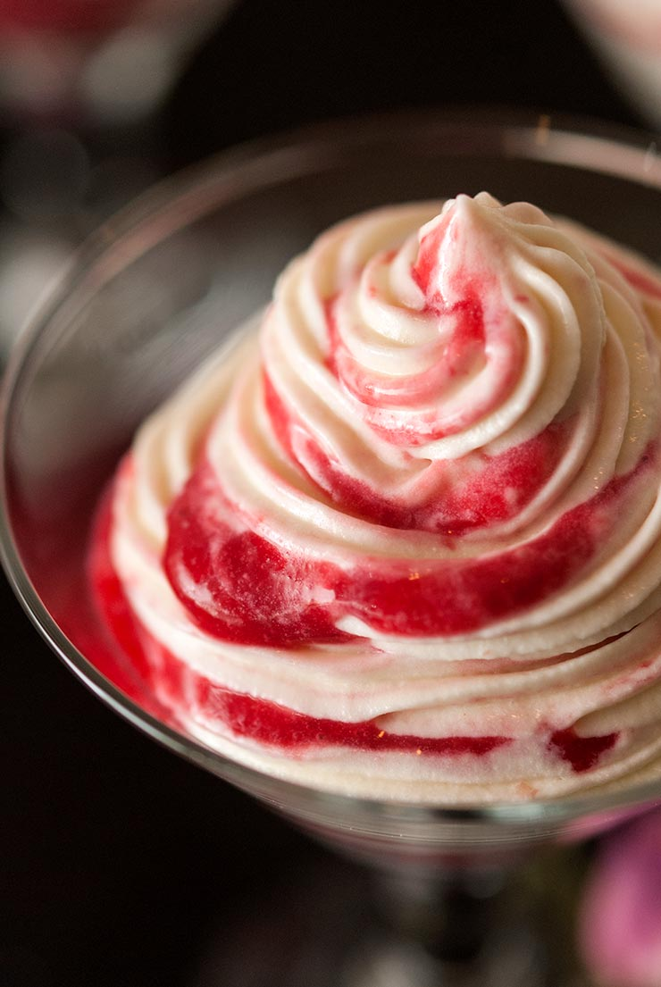 White chocolate mousse with raspberry swirls in a small glass.