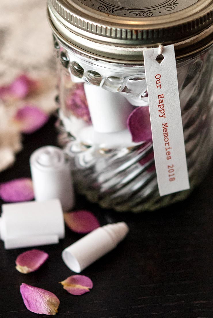 A jar with tiny scrolls inside and outside of it on a black table, sprinkled with rose petals.