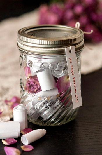 A jar with tiny scrolls inside and outside of it on a black table, sprinkled with rose petals. There is lace and pink roses behind it.