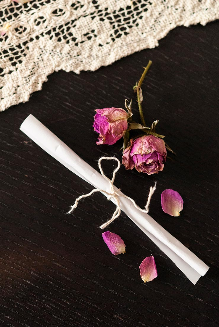 A small scroll of paper, tied with string, on a black table with sprinkled with rose petals beside a lace table cloth.