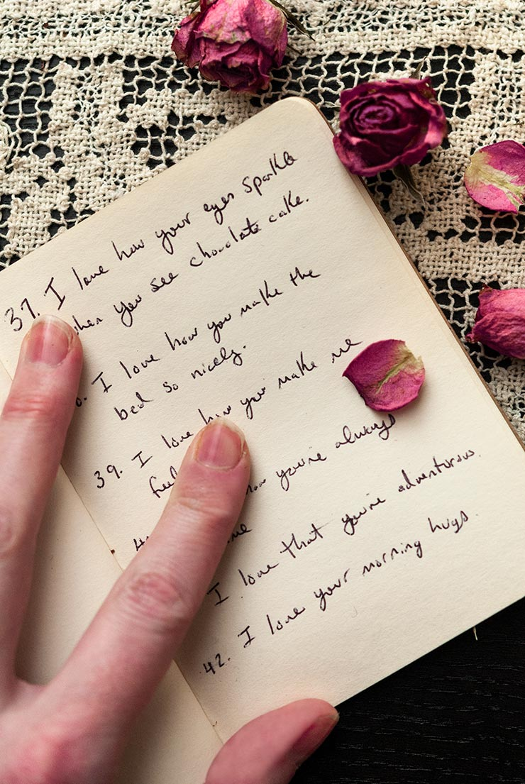 A hand holding open the pages of a book with writing inside on a lace table cloth, sprinkled with rose petals.