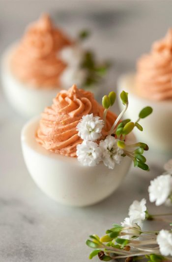 3 deviled eggs on a marble table with pink filling and garnished with baby's breath and sprouts.