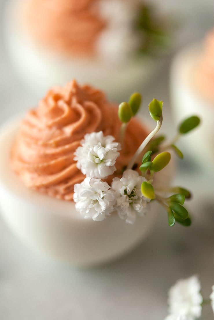 A closeup of a deviled egg on a marble table with pink filling and garnished with baby's breath and sprouts.