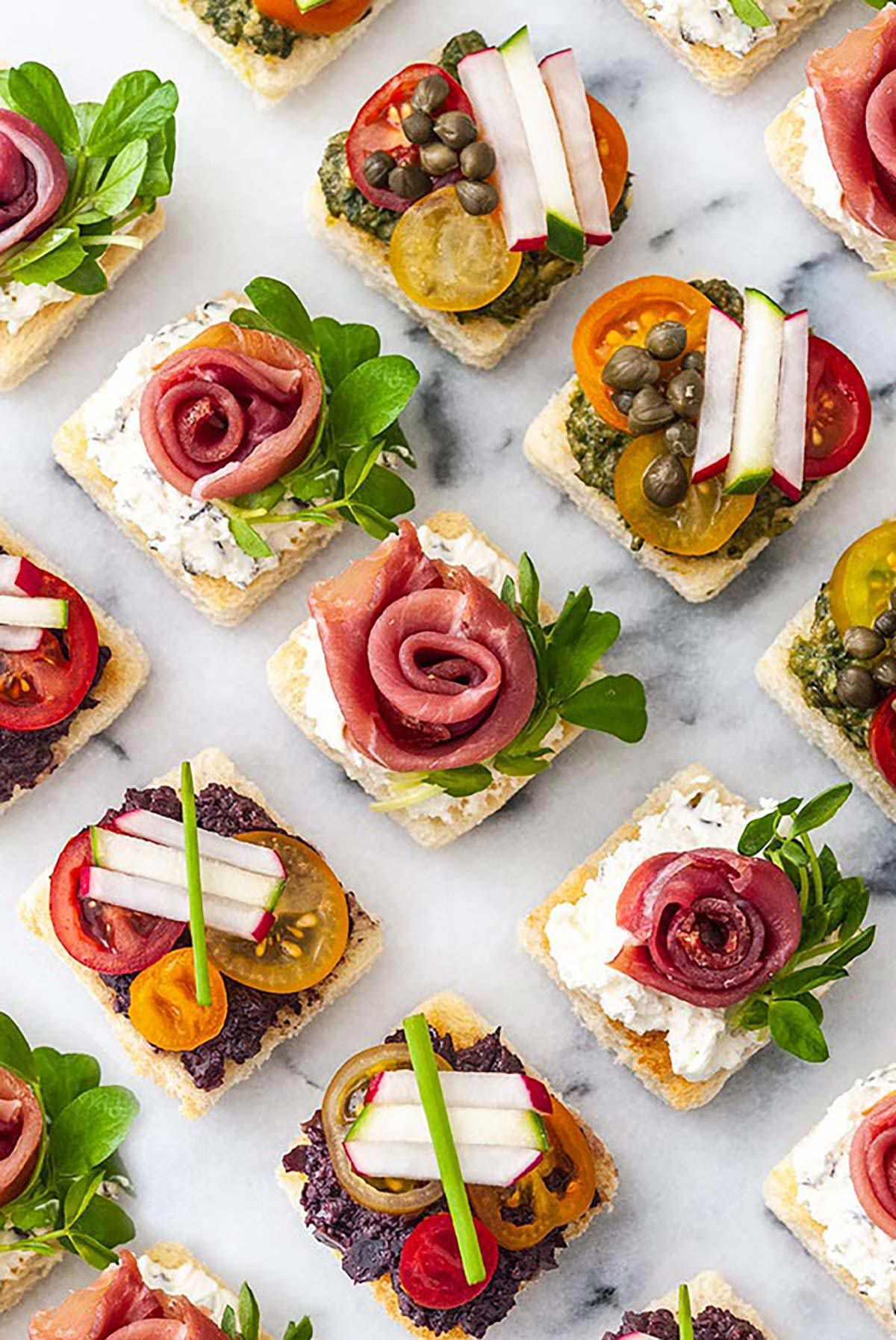 A marble appetizer tray of 15 canapés in 3 different styles.