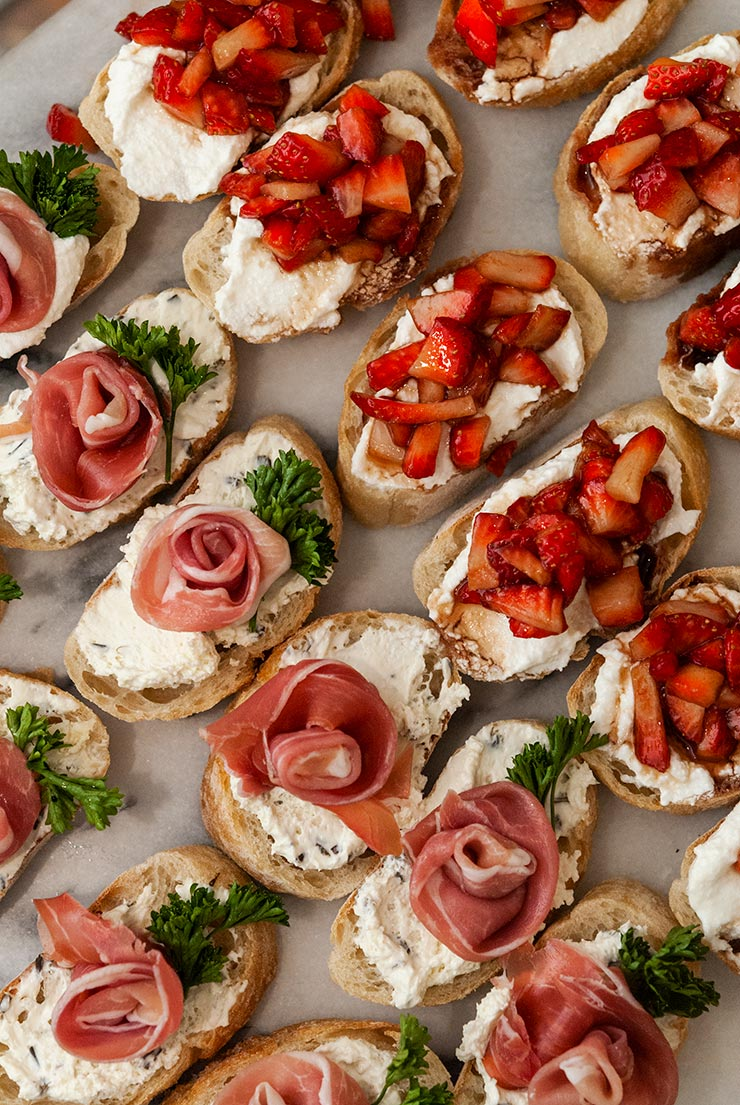 strawberry and prosciutto rose crostini on a marble table.