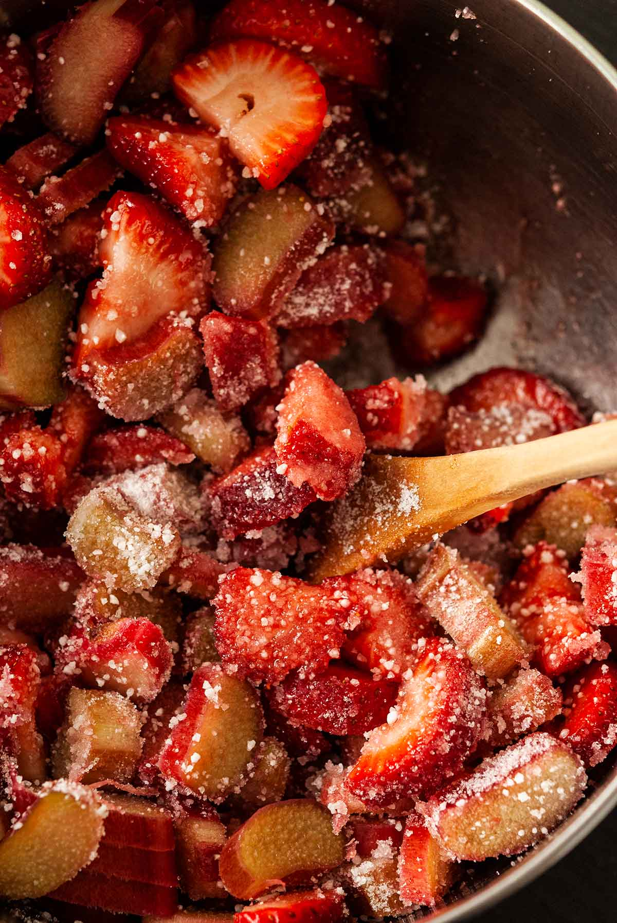 Raw strawberries and rhubarb in a mixing bowl with sugar and tapioca and a spoon.