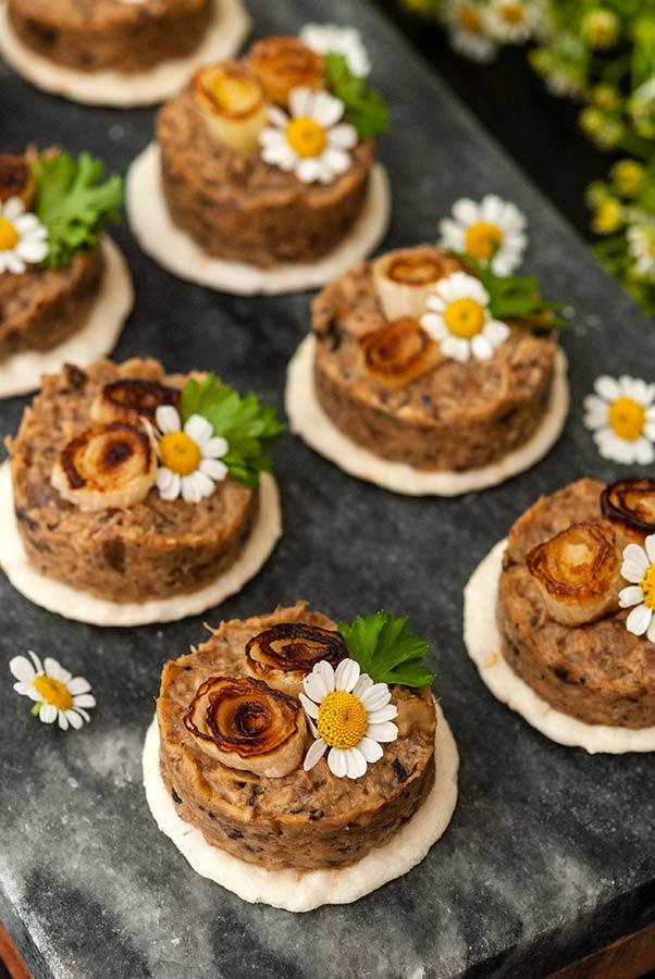 6 mushroom pâté canapés garnished with scallions and flowers on a marble slate.
