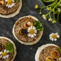 4 mushroom pâté canapés garnished with scallions and flowers on a marble slate.