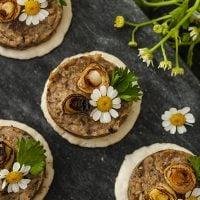 4 mushroom pâté canapés garnished with scallions and flowers on a marble slate.