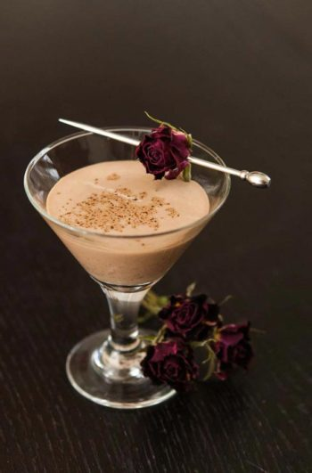 A small glass of Mexican Chocolate liqueur on a table, garnished with a dry rose with 3 roses at its base.