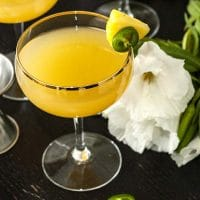 A pineapple cocktail on a table, garnished with pineapple and jalapeño, with tropical flowers in the background.