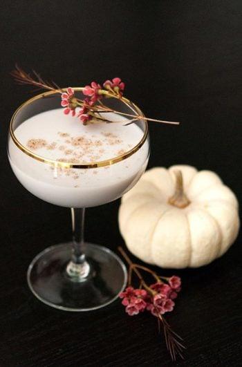 A white Pumpkin cocktail beside a small white pumpkin.