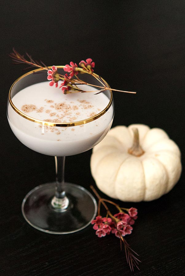A White Pumpkin cocktail on a table, garnished with a few flowers beside a small white pumpkin on a table.