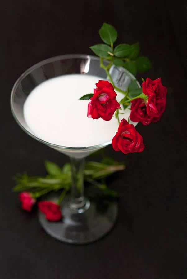 A White Rosemary Rose cocktail in a martini glass, garnished with small roses.