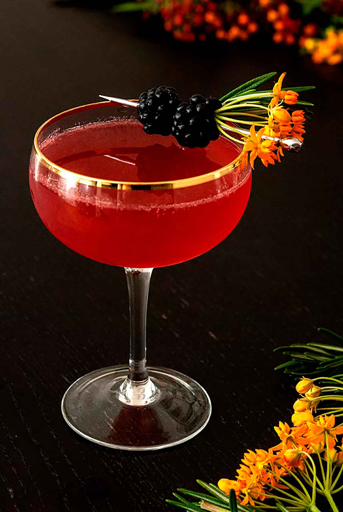 A cocktail on a wood table, garnished with flowers and blackberries.
