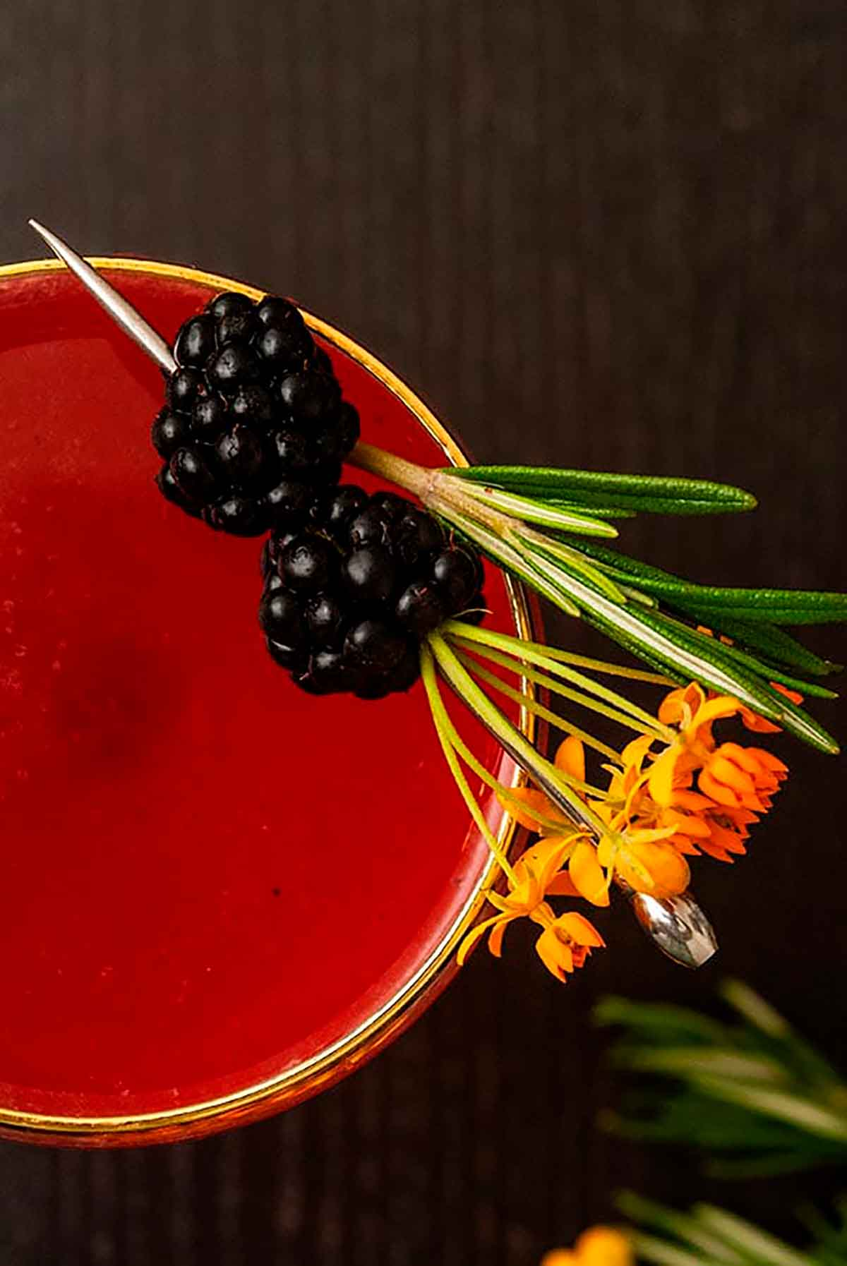 The top of a cocktail on a wood table, garnished with flowers and blackberries.