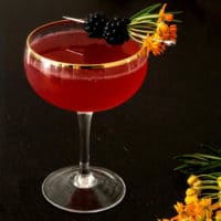 A cocktail on a wood table, garnished with flowers and blackberries with a few flowers on the table.