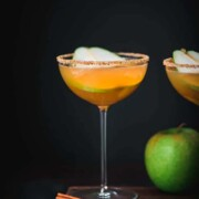 A martini garnished with a pear slice and a sugar rim beside a green apple.