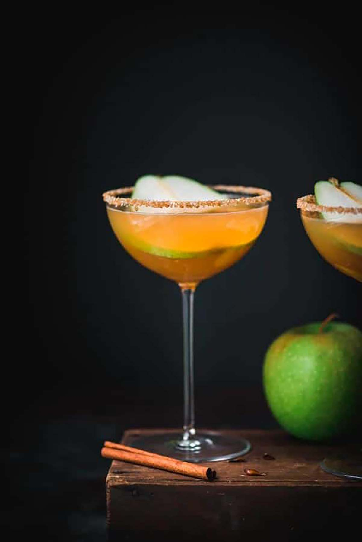A marktini garnished with a pear slice and a sugar rim beside a green apple.