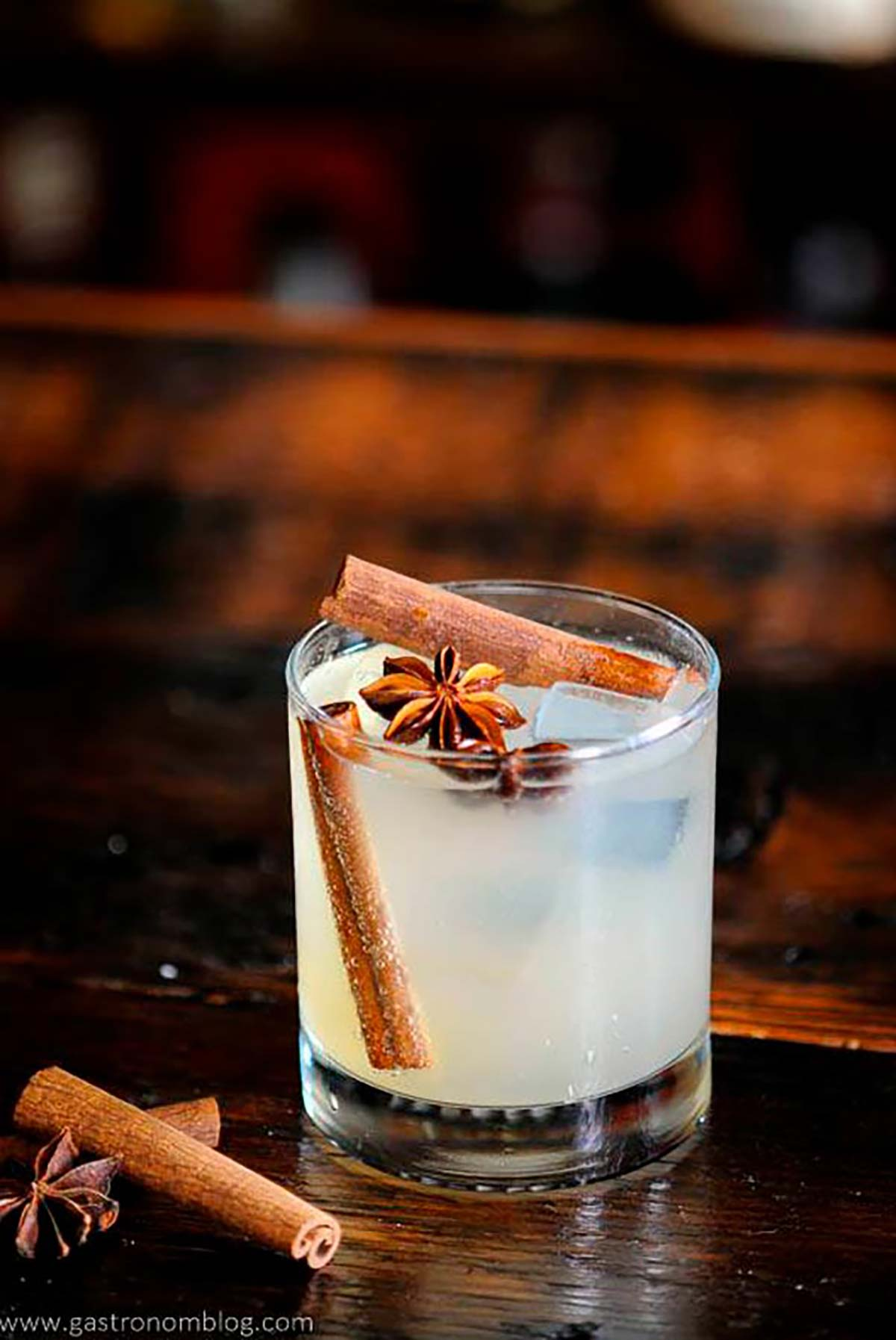 A cocktail garnished with cinnamon sticks and star anise on a table.