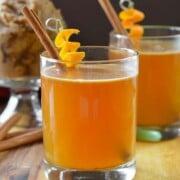 2 cocktails garnished with orange peels and cinnamon sticks.