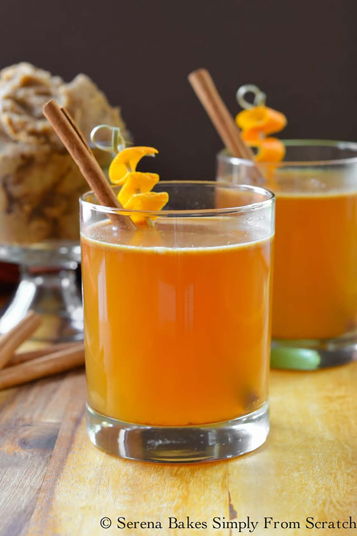 2 cocktails garnished with orange peels and cinnamon sticks.